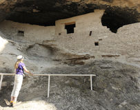 En kvinna undersöker grotta 2 på Gila Cliff Dwellings Arkivbilder