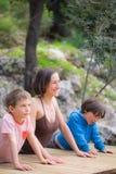 En kvinna utbildar med barn i g?rden royaltyfri foto