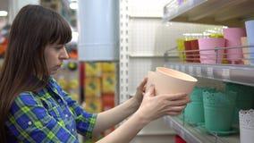 En kvinna väljer en blomkruka i en supermarket lager videofilmer