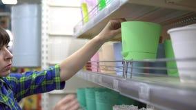 En kvinna väljer en blomkruka i en supermarket arkivfilmer