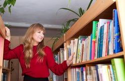 En kvinna väljer en bok i ett arkiv royaltyfria bilder