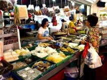 En kvinna väljer från en bred variation av ny mat från en marknad i staden av Tampines i Singapore Fotografering för Bildbyråer