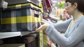 En kvinna väljer en textilask för lagring i en supermarket stock video