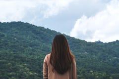 En kvinna vänder tillbaka och stå med blå himmel, den gröna naturen och berget royaltyfri foto