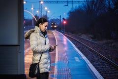 En kvinna wating för ett drev och använder en smartphone på en järnväg royaltyfria bilder