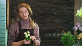 En kvinnablomsterhandlare i ett förkläde som står på räknaren i en blomsterhandel som förbereder en bukett av blommor stock video