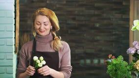 En kvinnablomsterhandlare i ett förkläde som står på räknaren i en blomsterhandel som förbereder en bukett av blommor arkivfilmer