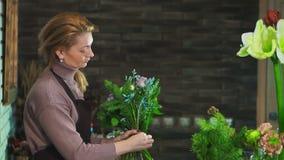 En kvinnablomsterhandlare i ett förkläde som står på räknaren i en blomsterhandel som förbereder en bukett av blommor lager videofilmer