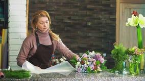 En kvinnablomsterhandlare i ett förkläde som står på räknaren i en blomsterhandel, slår in en bukett av blommor stock video