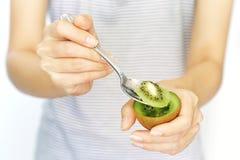 En kvinnahållkiwi och skiva med skeden för att äta på isolerad vit bakgrund begrepp av näring som är sunt, skönhet royaltyfri foto