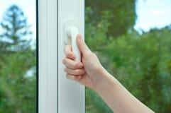 En kvinnahand öppnar fönsterramen av fönstret arkivbilder