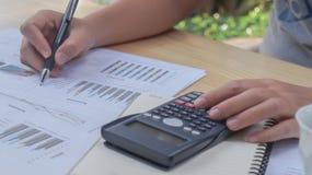 En kvinnahand använder en räknemaskin och beräknar om kostnaden hemma Begrepp för finansiell ledning Royaltyfria Bilder
