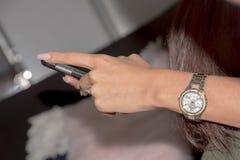 En kvinnahand med en klocka som rymmer en telefon Arkivfoto