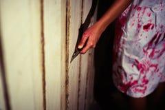 En kvinnainnehavkniv med blod, halloween begrepp arkivbild