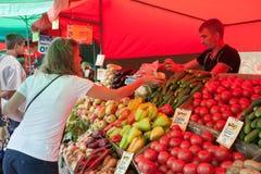 En kvinnaköpandefrukt i grönsakmässa Royaltyfri Bild