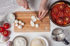 En kvinnakock skivar mozzarellaost för att göra en italiensk hemlagad pizza På den vita tabellen är mozzarellaen, pizzadeg och ga Royaltyfria Bilder