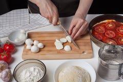 En kvinnakock skivar mozzarellaost för att göra en italiensk hemlagad pizza På den vita tabellen är mozzarellaen, pizzadeg och ga Fotografering för Bildbyråer