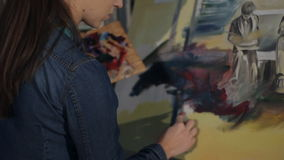 En kvinnakonstnär arbetar på en målningpalettkniv och olje- målarfärger lager videofilmer