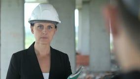 En kvinnakonstruktion som lyssnar till, är kollegan på kontorsbyggnad lager videofilmer