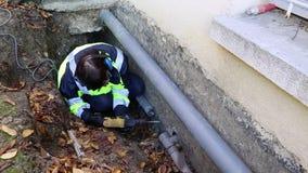 En kvinnarörmokare borrar ett hål i den yttre väggen av huset för att fixa rören stock video
