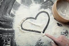 En kvinnas hand drar en hjärta på mjöl, ett romantiskt lynne arkivfoto
