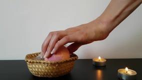 En kvinnas hand med härligt naturligt långt spikar tar ett bad bombarderar från korgen Atmosfären av avkoppling och lugn arkivfilmer