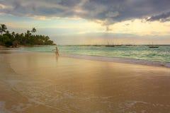 En kvinnaspring på stranden på solnedgången royaltyfri fotografi