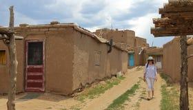 En kvinnaturist går en gata i den Taos puebloen Royaltyfri Bild