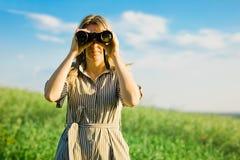 En kvinnautforskare använder utomhus- svart kikare - royaltyfri bild