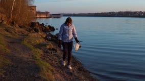 En kvinnavolontär samlar avskräde på kusten av behållaren lager videofilmer