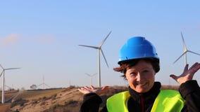 En kvinnlig arbetare mot en bakgrund av vindturbiner lager videofilmer