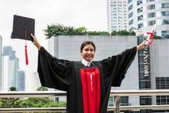 En kvinnlig asiatisk student i avläggande av examenkappan som rymmer diplomet arkivfoton