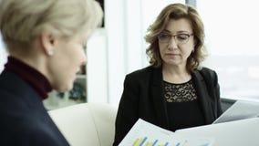 En kvinnlig chef framl?gger nytt projektplan till kollegor p? m?te som in f?rklarar id?er p? flipchart till coworkers stock video