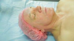 En kvinnlig cosmetologist i handskar applicerar en behandlingmaskering till en framsida för man s med en borste Slapp fokus stock video