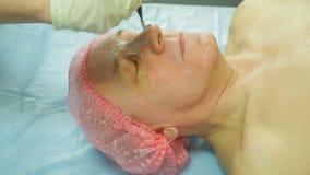 En kvinnlig cosmetologist i handskar applicerar en behandlingmaskering till en framsida för man s med en borste stock video
