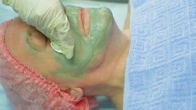 En kvinnlig cosmetologist tar bort en terapeutisk gyttjamaskering från en man'sframsida med ett bomullsblock arkivfilmer