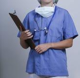 En kvinnlig doktor med en mapp och ett mskanseende arkivfoto