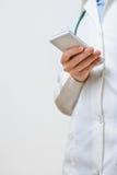 En kvinnlig doktor som smsar på smartphonen Royaltyfri Foto