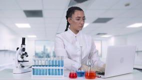 En kvinnlig forskare skriver data för kliniskt försök till en bärbar dator, medan sitta på en vit tabell i ett kemiskt laboratori stock video