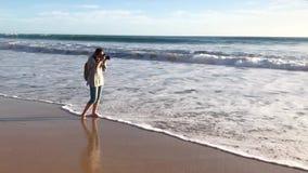 En kvinnlig fotograf går barfota längs stranden, stoppar och tar ett skott stock video