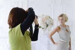 En kvinnlig fotograf tar en härlig modell i studion fotografering för bildbyråer