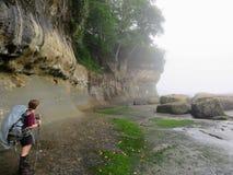 En kvinnlig fotvandrare som navigerar försiktigt kustlinjen längs västkustenslingan arkivbild