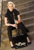 Den kvinnliga gataaktören sitter kliver på klarinettfallet med spetsar royaltyfri fotografi