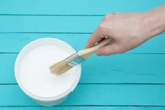 En kvinnlig hand tappar en målarpensel in i en hink med vit målarfärg arkivbild
