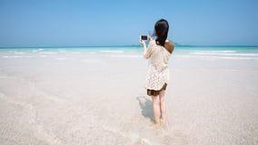 En kvinnlig handelsresande tar bilden av turkoshavet med en mobiltelefonkameraJeju ö fotografering för bildbyråer