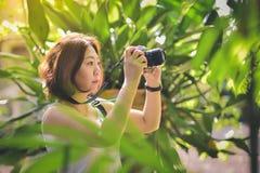 En kvinnlig handelsresande tar lyckligt bilder med naturen arkivfoton