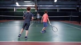 En kvinnlig instruktör i sportar som dräkten undervisar att spela medelåldersa pojkar för tennis itu, grabbar, studsar bollar på  lager videofilmer