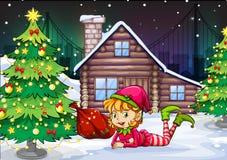 En kvinnlig jultomtenälva nära julträdet Fotografering för Bildbyråer
