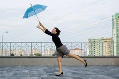En kvinnlig kör bak ett paraply mot bakgrunden av staden Royaltyfri Foto