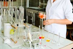 En kvinnlig laborant, en doktor, en kemist, arbeten med flaskor, provrör, gör lösningar, mediciner, blandningingredienser arkivfoton